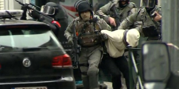 In this framegrab taken from VTM, armed police officers escort a suspect to a police vehicle during a raid in the Molenbeek neighborhood of Brussels, Belgium, Friday March 18, 2016. After an intense four-month manhunt across Europe and beyond, police on Friday captured Salah Abdeslam, the top fugitive in the Paris attacks in the same Brussels neighborhood where he grew up. (VTM via AP) BELGIUM OUT