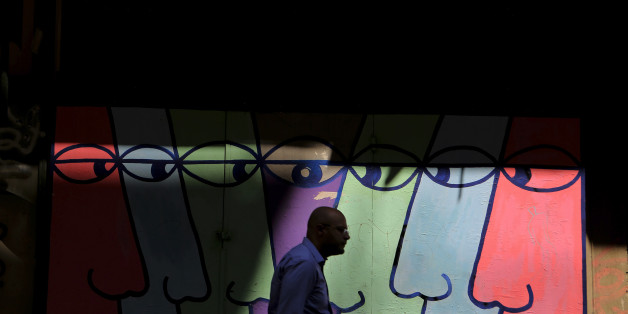 A pedestrian walks in front of  a mural in central Athens, Monday, Aug. 26, 2013. In two bailout packages so far, Greece's European partners and the International Monetary Fund have committed euro 240 billion (US$320 billion) in loans. Last week, German Finance Minister Wolfgang Schaeuble said there will have to be another aid program after the current one expires next year. (AP Photo/Petros Giannakouris)