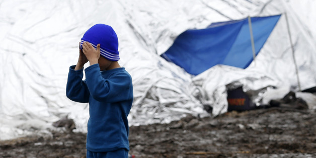 A migrant boy fixes his woolen hat in an improvised camp on the border line between Macedonia and Serbia near the northern Macedonian village of Tabanovce, Friday, March 11, 2016.  About 1,500 refugees remain stranded at the Macedonian border with Serbia as the borders on the Balkan migrant route are closing. (AP Photo/Darko Vojinovic)
