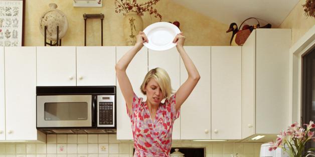 Woman smashing plates in kitchen