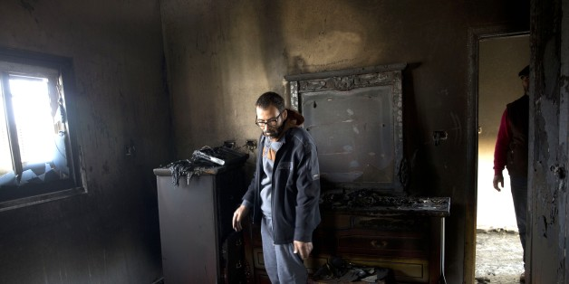 A Palestinian man inspects a house that was torched in the Palestinian village of Duma near the West Bank city of Nablus, Sunday, March 20, 2016. A Palestinian home near the site of an arson attack that killed three Palestinians last year caught fire early Sunday, Israeli and Palestinian officials said, with immediate suspicion falling on Jewish extremists. (AP Photo/Majdi Mohammed)