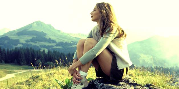 Woman sitting on mountainside