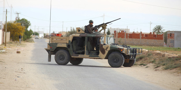 Tunisian soldiers ride an humvee as they search for attackers still at large in the outskirts of Ben Guerdane, southern Tunisia, Tuesday, March 8, 2016.  (AP Photo)