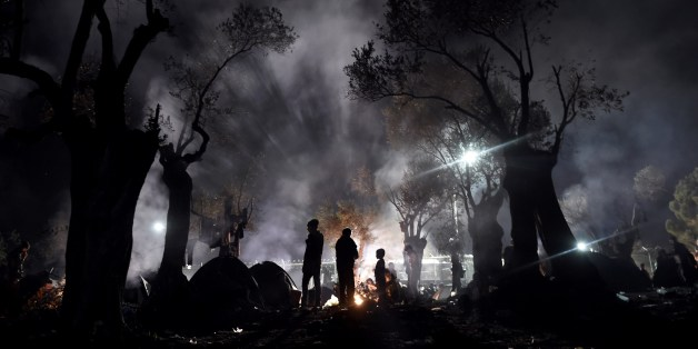 Refugees and migrants spend the night in a field outside of the Moria Hot Spot, on the Greek island of Lesbos on November 9, 2015. More than 3,000 refugees and migrants have drowned among the nearly 800,000 who have reached Europe this year. However, EU states have bickered for months over a joint solution, particularly over plans to relocate a total of 160,000 asylum seekers from frontline countries to other parts of the EU bloc.  / AFP / ARIS MESSINIS        (Photo credit should read ARIS MESSINIS/AFP/Getty Images)