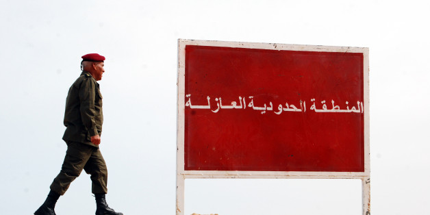 "A Tunisian soldier walks on a sandbank near a board saying ""no-man's land, buffer zone"" during a presentation of the anti-jihadi fence, in near Ben Guerdane, eastern Tunisia, close to the border with Libya, Saturday, Feb. 6, 2016. Tunisia's defense minister has visited an anti-jihadi fence that's being built on the country's border with Libya to stop Islamist militants from entering Tunisian territory. Defense Minister Farhat Horchani inspected the first completed part of the 196-kilometer (122-mile) fence Saturday, which aims to counter the threat from jihadi militants and render the entire border impassable by vehicles. Horchani said the project came about with financial assistance from Germany and the U.S. (AP Photo/Benjamin Wiacek)"