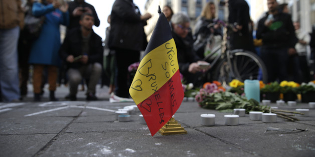 A Belgian flag reading 'We are all Brussels' stands at a makeshift memorial at Place de la Bourse (Beursplein) following attacks in Brussels on March 22, 2016. Airlines cancelled hundreds of flights and European railways froze links with Brussels after a series of bomb blasts killed around 35 people in the city's airport and a metro train, sparking a broad security response. AFP PHOTO / KENZO TRIBOUILLARD / AFP / KENZO TRIBOUILLARD        (Photo credit should read KENZO TRIBOUILLARD/AFP/Getty Images)