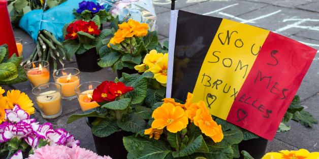 A memorial to attack victims with a Belgian flag and flowers is set up outside the stock exchange in Brussels on Tuesday, March 22, 2016. Explosions, at least one likely caused by a suicide bomber, rocked the Brussels airport and subway system Tuesday, prompting a lockdown of the Belgian capital and heightened security across Europe. (AP Photo/Geert Vanden Wijngaert)