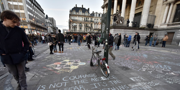 People write hundreds of messages on the asphalt at Place de la Bourse in the center of Brussels to mourn for the victims of todays attack, Tuesday, March 22, 2016. Bombs exploded at the Brussels airport and one of the city's metro stations Tuesday, killing and wounding scores of people, as a European capital was again locked down amid heightened security threats. (AP Photo/Martin Meissner)
