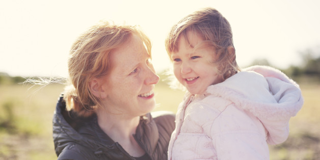 A happy mother and daughter in a park backlit by autumn sunshine.