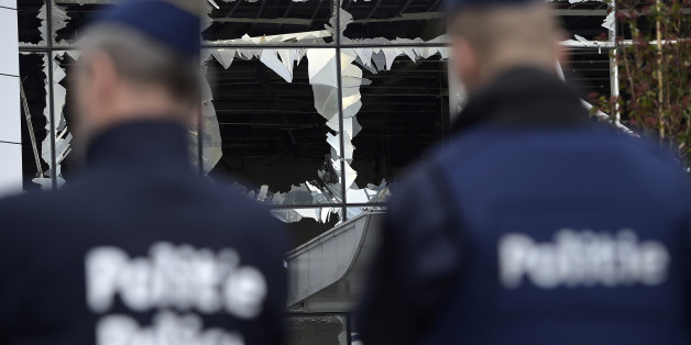 Two police officers stand in front of blown out windows at Zaventem Airport in Brussels on Wednesday, March 23, 2016. Belgian authorities were searching Wednesday for a top suspect in the country's deadliest attacks in decades, as the European Union's capital awoke under guard and with limited public transport after scores were killed and injured in bombings on the Brussels airport and a subway station. (AP Photo/Yorick Jansens, Pool photo via AP)