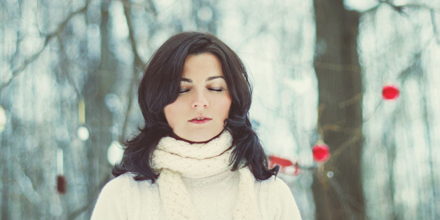 Girl with shut eyes in winter forest