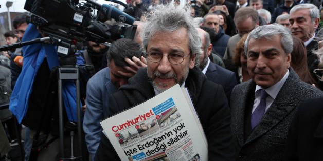 Can Dundar, the editor-in-chief of opposition newspaper Cumhuriyet, center, speaks to the media before the start of his trial in Istanbul, Friday, March 25, 2016. A group of writers, including Nobel laureates, are calling on Turkey to drop charges against two prominent journalists who face life imprisonment for their reports, and to end its crackdown on free expression. Dundar and Erdem Gul, paper's Ankara representative, go on trial on Friday accused of espionage and other charges for their rep