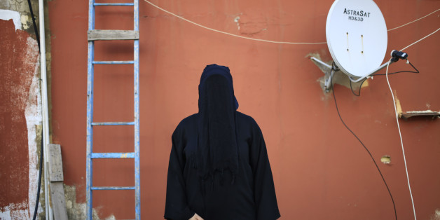 This Friday, May 1, 2015 shows a 32-year old Lebanese woman, whose father is a Shiite Muslim and mother is a Sunni Muslim, posing for a photograph, on the roof of her home in Beirut, Lebanon. For most, the niqab is a choice. They do so out of their own interpretation of the Quran and the hadith, a collection of traditions and anecdotes about the Prophet Muhammad, believing that a woman's body should be covered out of modesty. (AP Photo/Hassan Ammar)