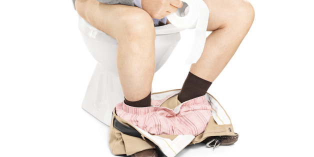 Studio shot of the legs of a man sitting on a toilet isolated on white background