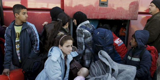 Migrants and refugees pack their belongings into a bus at a makeshift camp at the Greek-Macedonian border near the village of Idomeni, Greece, March 25, 2016. REUTERS/Marko Djurica
