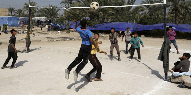 Teenagers who fled from Tikrit, Iraq, because they feared Islamic State militants play volleyball at a refugee camp outside Baghdad, Iraq, Wednesday, March 18, 2015. (AP Photo/Karim Kadim)