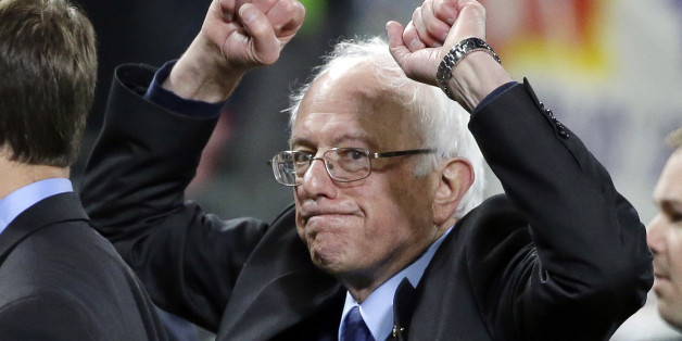 Democratic presidential candidate Sen. Bernie Sanders, I-Vt., pumps his fists as he leaves the field after speaking at a rally Friday, March 25, 2016, in Seattle. (AP Photo/Elaine Thompson)