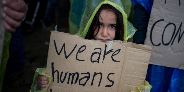 A girl holds a placard during a protest held by migrants and refugees to call for the reopening of the borders at a makeshift camp at the Greek-Macedonian border near the village of Idomeni on March 23, 2016. 