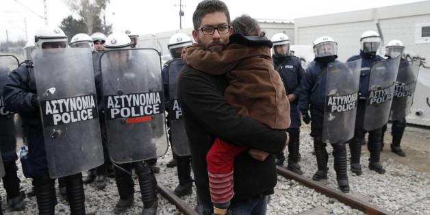 Ein Flüchtling harrt vor griechischen Polizisten an der Grenze aus.