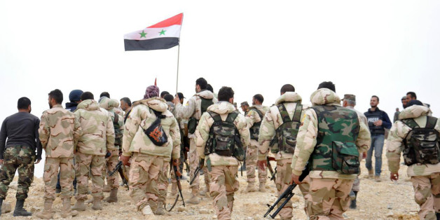 In this photo released by the Syrian official news agency SANA, Syrian soldiers gather around a Syrian national flag in Palmyra, Syria, Sunday, March 27, 2016. Syrian state media and an opposition monitoring group say government forces backed by Russian airstrikes have driven Islamic State fighters from the historic central town of Palmyra, held by the extremists since May. (SANA via AP)