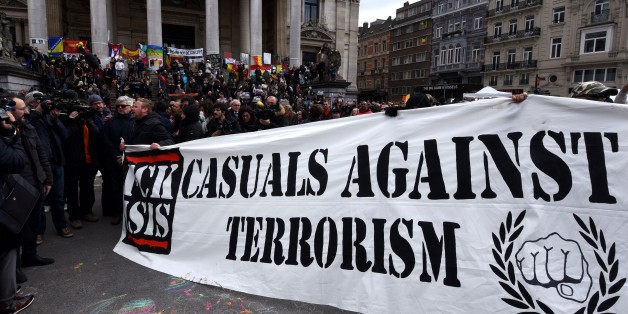 A group of people march behind a banner of the 'FCK-Casuals' hooligan movement, as they arrive in the square outside the stock exchange in Brussels on March 27, 2016 as tensions mounted after the square was invaded by some 200 far-right football hooligans. 