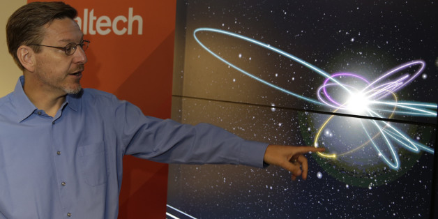 """California Institute of Technology astronomer Michael Brown points to a yellow dot simulating Planet 9 on a computer video simulation view of Planet 9 in the solar system at the CalTech USGS Media center in Pasadena, Calif., on Wednesday, Jan. 20, 2016. Scientists reported Wednesday, they finally have """"good evidence"""" for Planet 9, a true ninth planet on the fringes of our solar system. The gas giant is thought to be almost as big as Neptune and orbiting billions of miles beyond Neptune's path, distant enough to take 10,000 to 20,000 years to circle the sun. Planet 9, as the two Caltech researchers call it, hasn't been spotted yet. They base their findings on mathematical and computer modeling, and anticipate its discovery via telescope within five years. (AP Photo/Damian Dovarganes)"""