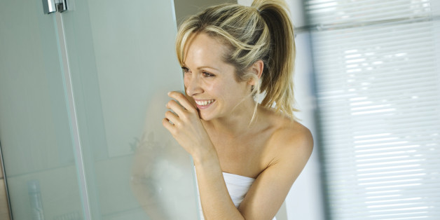 Young smiling woman wrapped in towel in bathroom