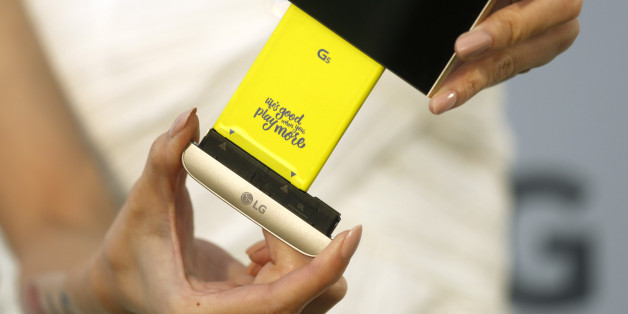 A model poses for photographs with LG Electronics' new smartphone G5 and its removable battery during its launch event in Taipei, Taiwan March 24, 2016. REUTERS/Tyrone Siu