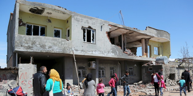 People stand in front of a building, which was damaged during the security operations and clashes between Turkish security forces and Kurdish militants, in the southeastern town of Idil, Turkey, March 31, 2016. REUTERS/Sertac Kayar