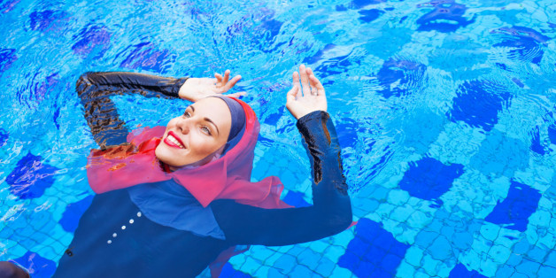 muslim woman in red hijab swimming in a pool (lying on a back)