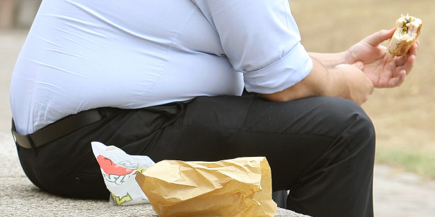File photo dated 28/07/10 of an overweight man eating, as it was proposed that GPs should be paid to measure their patients' BMI.