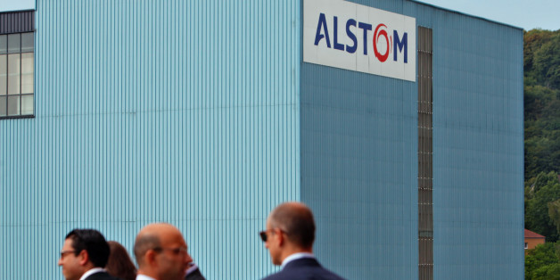 People chat in front of the Alstom plant in Belfort, eastern France, Tuesday, June 24, 2014. Alstom's chief executive said the French heavy engineering firm's agreement to sell off most of its power generation business to U.S. rival General Electric Co. will save jobs and protect France's national interests. The $17 billion deal was agreed over the weekend after weeks of international negotiations that reached the highest levels of French politics. (AP Photo/Thibault Camus)