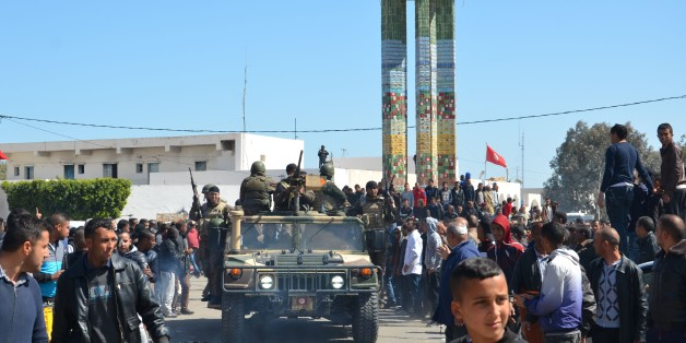 Tunisians wave to a military convoy during a visit of the prime minister in Ben Guerdane on March 13, 2016, a week after jihadists launched a wave of attacks on army and police posts in the border town. / AFP / FATHI NASRI        (Photo credit should read FATHI NASRI/AFP/Getty Images)