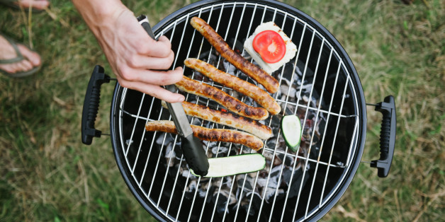 Hand at barbeque grill with sausages grill cheese and zucchini