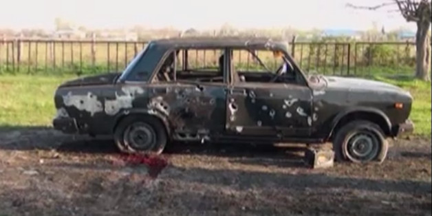 In this image from TV, a car destroyed with blood showing in the aftermath after heavy fighting erupted in Terter, Azerbaijan, Saturday April 2, 2016, between Armenian and Azerbaijani forces over the separatist region of Nagorno-Karabakh.  Russia expressed grave concern on Saturday over the recent military conflict along the Azerbaijan-Armenia border, calling on all parties involved to stop fighting and exercise restraint. Officials from each of the former Soviet republics blamed the other on Sa