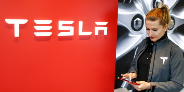 A Tesla employee stands beside a company logo in the dealership in Berlin, Germany, November 18, 2015. REUTERS/Hannibal Hanschke