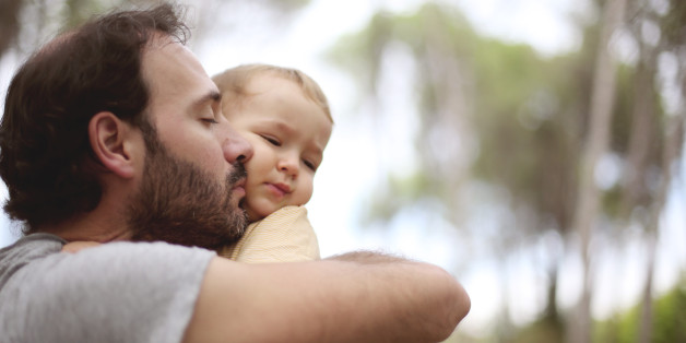 Dad kissing uncomfortable boy