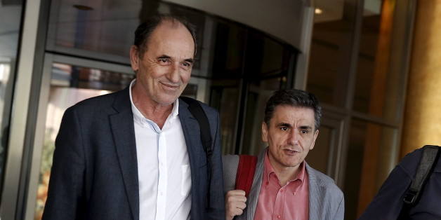 Greek Economy Minister George Stathakis (L) and Finance Minister Euclid Tsakalotos leave a hotel following an overnight meeting with representatives of the International Monetary Fund, the European Commission, the European Central Bank and the eurozone's rescue fund, the European Stability Mechanism in Athens, August 11, 2015. Greece and its international lenders clinched a multi-billion-euro bailout agreement on Tuesday after marathon talks through the night, officials said, raising hopes aid can be disbursed in time for a major debt repayment falling due in days.  REUTERS/Alkis Konstantinidis