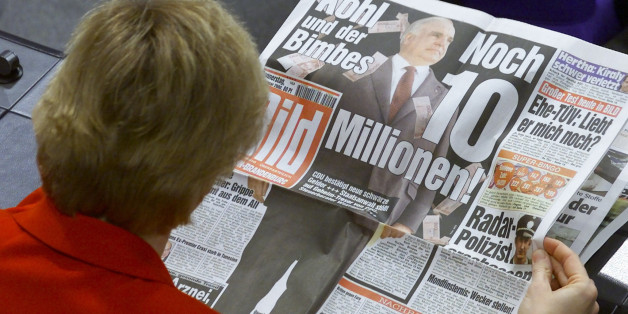"An unidentified Christian Democratic (CDU) member of the Bundestag lower house of parliament reads the front page of Germany's biggest daily newspaper ""Bild"" ahead of a parliamentary debate in the Reichstag in Berlin January 20. The headline in ""Bild"" reads ""Kohl and the cash. Another ten million"". Wolfgang Schaeuble, leader of Germany's scandal-stricken oppostion CDU apologised to parliament for misleading the chamber over a cash donation he accepted from a fugitive arms leader.