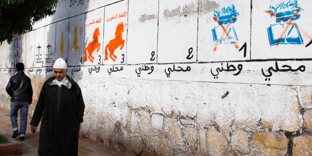 A man walks past electoral paintings representing political parties in Casablanca, Morocco, Thursday, Nov. 24, 2011. Moroccans head to polls to elect a new parliament Friday after the king brought forward elections in response to Arab Spring demonstrations over the past nine months. (AP Photo/Abdeljalil Bounhar)