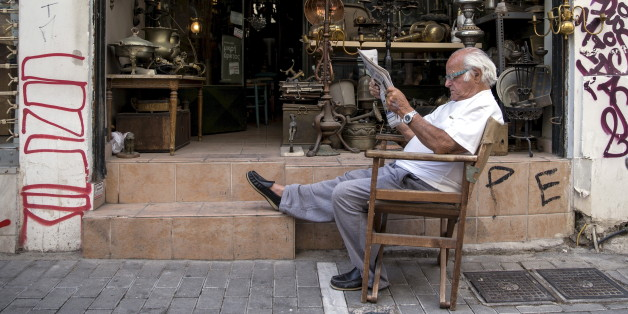 """A vendor reads newspaper in front of his shop in Athens, Greece June 27, 2015. Greek Prime Minister Alexis Tsipras called a referendum on bailout demands from foreign creditors on Saturday, rejecting an """"ultimatum"""" from lenders and putting a deal that could determine Greece's future in Europe to a risky popular vote. REUTERS/Marko Djurica"""