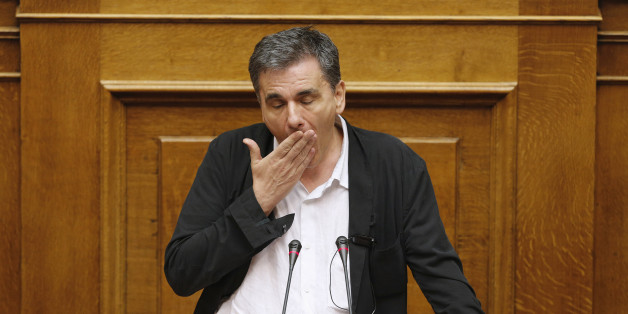 Greek Finance Minister Euclid Tsakalotos reacts as deputies attempt to disrupt his speech during a night parliamentary session in Athens, Greece, early August 14, 2015. Greek lawmakers debated a draft bill on the latest bailout deal, which the government hopes will be approved ahead of a euro zone finance ministers meeting in Brussels on Friday. REUTERS/Christian Hartmann      TPX IMAGES OF THE DAY