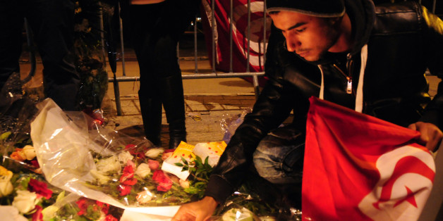 Tunisian citizens leave flowers and light up candles at Mohamed V avenue in memory of the 12 martyrs. The Islamic State group claimed responsibility for Tuesday's attack on a bus in central Tunis, which left 12 dead plus the attacker. (AP Photo/Riadh Dridi)