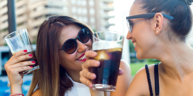 Frauen trinken Cola.