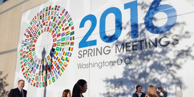 People are seen in front of a banner during the 2016 International Monetary Fund, World Bank Spring Meetings at IMF headquarters on April 14, 2016. / AFP / MANDEL NGAN        (Photo credit should read MANDEL NGAN/AFP/Getty Images)