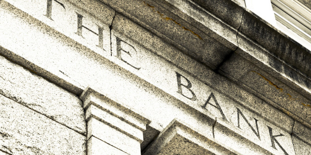 A detail view of the words THE BANK chiseled in stone.