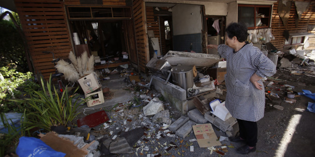 A local resident cleans up her house in Mashiki, Kumamoto prefecture, southern Japan, Friday, April 15, 2016. Aftershocks rattled communities in southern Japan as businesses and residents got a fuller look Friday at the widespread damage from an unusually strong overnight earthquake. (AP Photo/Koji Ueda)