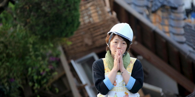 A woman reacts in front of collapsed house caused by an earthquake in Mashiki town, Kumamoto prefecture, southern Japan, in this photo taken by Kyodo April 16, 2016.  Mandatory credit REUTERS/Kyodo ATTENTION EDITORS - FOR EDITORIAL USE ONLY. NOT FOR SALE FOR MARKETING OR ADVERTISING CAMPAIGNS. THIS IMAGE HAS BEEN SUPPLIED BY A THIRD PARTY. IT IS DISTRIBUTED, EXACTLY AS RECEIVED BY REUTERS, AS A SERVICE TO CLIENTS. MANDATORY CREDIT. JAPAN OUT. NO COMMERCIAL OR EDITORIAL SALES IN JAPAN.      TPX I
