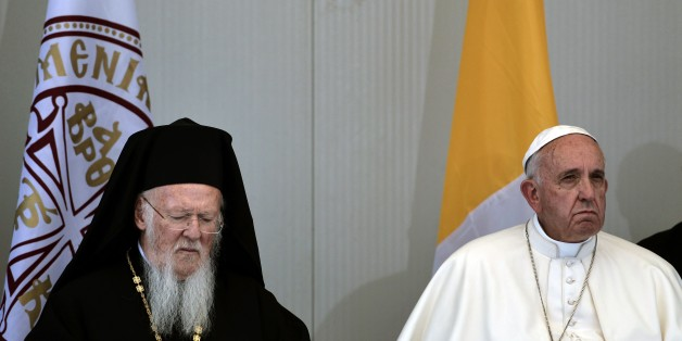 Patriarch Bartholomew (L) sits next to Pope Francis during their visit at the Moria detention center in Mytilene on April 16, 2016.Twelve Syrian refugees were accompanying Pope Francis on his return flight to Rome after his visit to Lesbos on Saturday and will be housed in the Vatican, the Holy See said. / AFP / ARIS MESSINIS        (Photo credit should read ARIS MESSINIS/AFP/Getty Images)