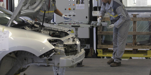 Employees work in the new Renault factory in Oran, west of Algiers November 10, 2014. French carmaker Renault said on Monday it was targeting annual production capacity of 25,000 vehicles at a new plant in Oran, Algeria, and that it was considering increasing this to 75,000 vehicles. Renault, which said it was Algeria's biggest carmaker with a market share of more than 25 percent, owns 49 percent of the plant and has made an initial investment of 50 million euros ($62 million), it said in a stat